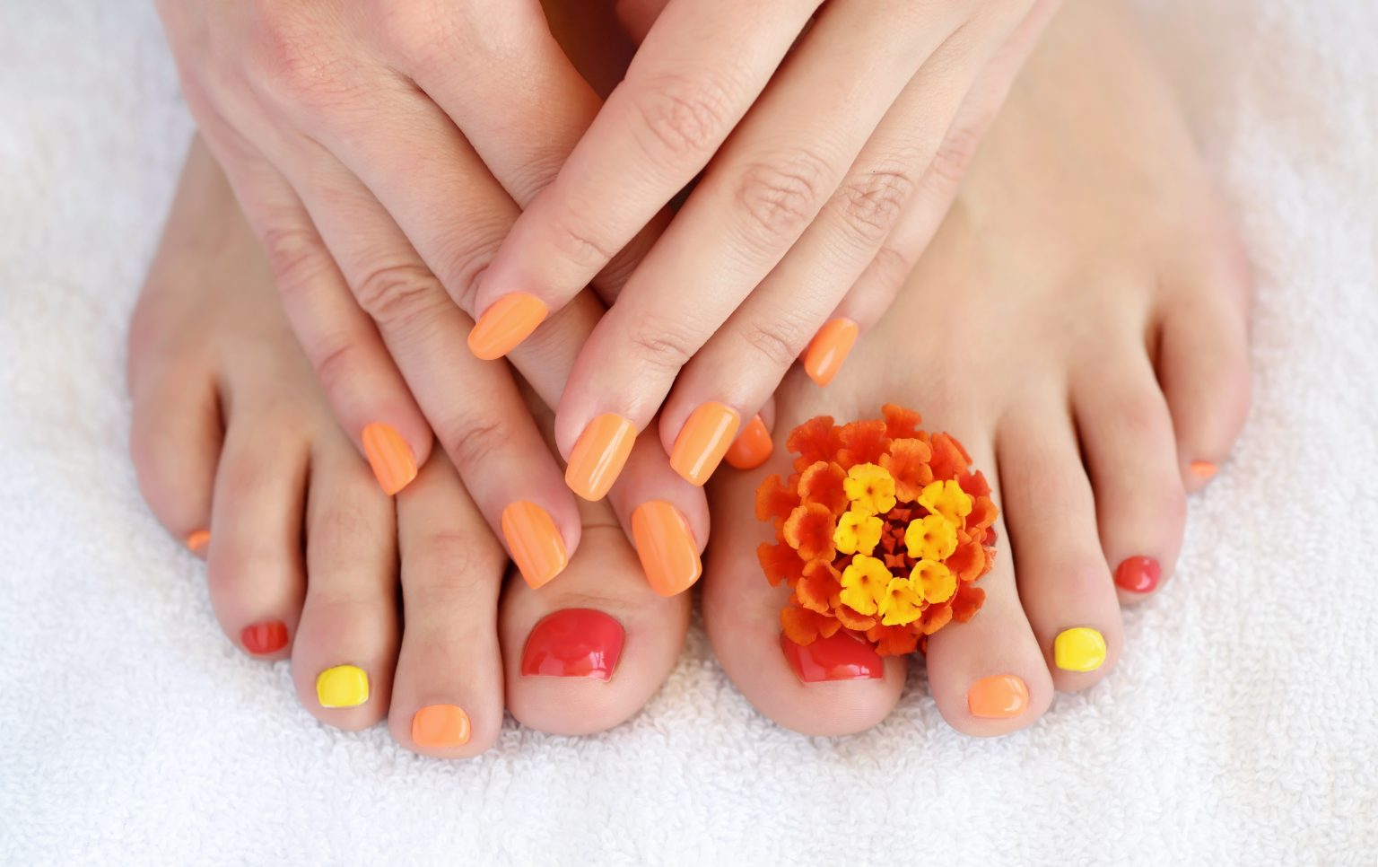 Female feet and hands with colorful manicure with red-orange flowers. Soft focus image